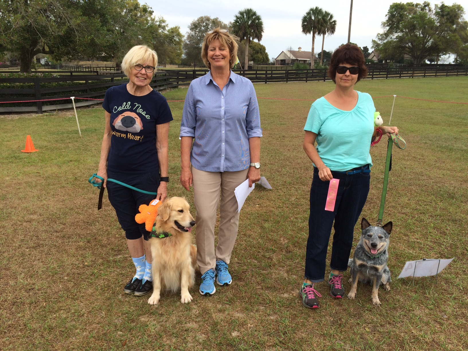 Deborah Dean (right) and her Australian Cattle Dog Timber Iselin and second place Barbara Anderson (left) and her Golden Retriever Emma (Magik Circle of Life). Judge Ellen Barktus (center).