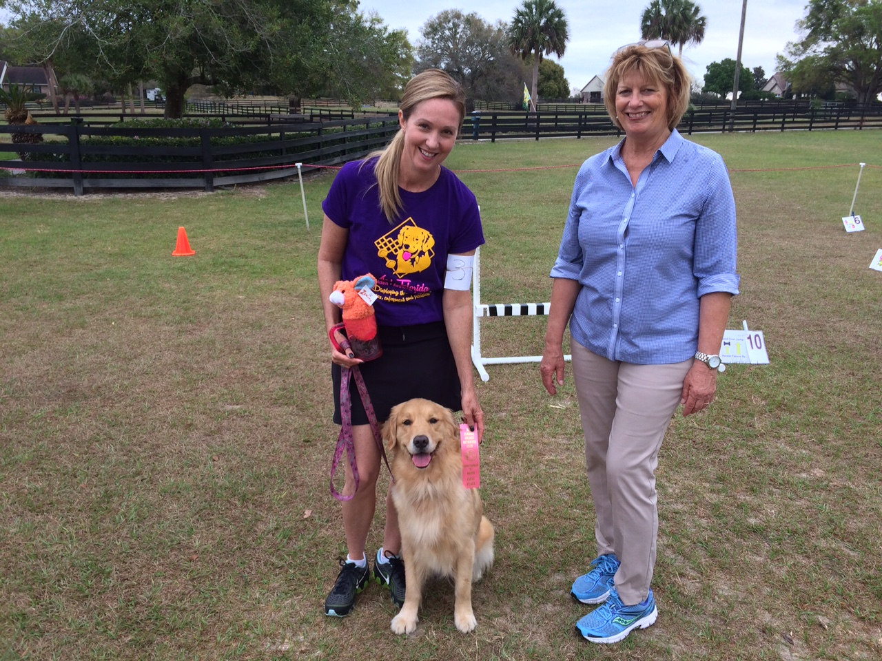 Michele Throm with her Golden Retriever Bella (Magik's Emerald Belle Of The Ball). Judge Ellen Barktus (right).